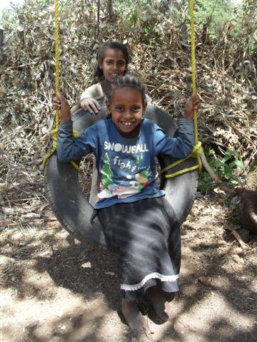 schoolgirls enjoy playing on the swing