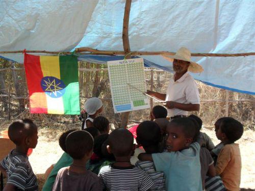Asenake teaches children to recite the Amharic fidel